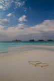 Zwei Herzen gezeichnet in den Sand am tropischen Strand lizenzfreie stockfotos