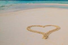 Zwei Herzen gezeichnet in den Sand am tropischen Strand stockbild