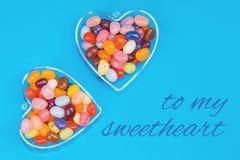 Zwei Herzen mit Süßigkeiten auf blauem Hintergrund stockfotografie