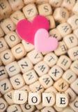 Zwei Herzen mit Wort-Liebe in Alphabet-Hintergrund-Weinlese-Ton, V Stockbilder