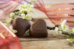 Zwei Herzen Schokolade mit einem roten Band und einer Blütenniederlassung O Stockfotografie
