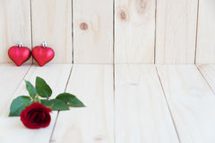 Zwei Herzen und Rotrose auf hölzernem Hintergrund Stockbilder