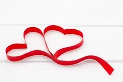 Zwei Herzen vom roten Band auf weißem hölzernem Hintergrund Stockbild