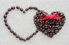 Zwei Herzen von Kaffeebohnen auf einer strukturierten Tasche Stockfotografie