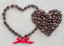 Zwei Herzen von Kaffeebohnen auf einer strukturierten Tasche Stockbilder