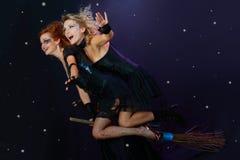 Zwei Hexen, die auf Besen fliegen stockbild