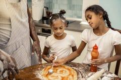 Zwei hilfreiche Mädchen, die Tomatensauce beim Kochen der Pizza verbreiten stockfoto