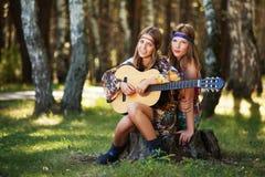 Zwei Hippiemädchen mit Gitarre in einem Sommerwald Stockbild