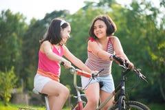 Zwei hispanische Kinder, die auf Fahrräder fahren Stockfotografie