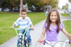 Zwei hispanische Kinder, die Fahrräder im Park reiten Stockbild
