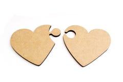 Zwei hölzerne Herzen in der Form des Puzzlespiels auf weißem Hintergrund Stockbild