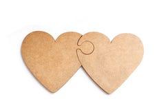 Zwei hölzerne Herzen in der Form des Puzzlespiels auf weißem Hintergrund Lizenzfreie Stockfotos