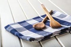 Zwei hölzerne kochende Löffel auf blauem Tuch auf Holztisch Stockfoto