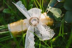 Zwei Hochzeitsringe auf Brautblumenstrauß Stockfotos