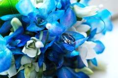 Zwei Hochzeitsringe auf einem Hochzeitsblumenstrauß Stockfotografie