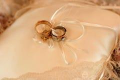 Zwei Hochzeitsringe auf einem Kissen Lizenzfreies Stockfoto