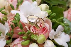 Zwei Hochzeitsringe auf rosafarbener Blume des Rosas lizenzfreies stockbild