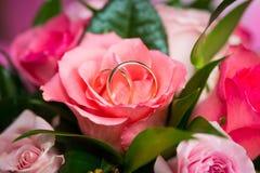 Zwei Hochzeitsringe auf stiegen in Brautblumenstrauß Stockfotos