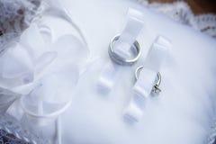 Zwei Hochzeitsringe im Farbband auf Kissen Stockfotos
