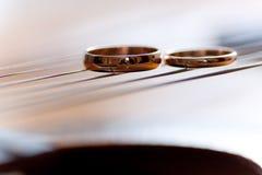 Zwei Hochzeitsringe sind auf Gitarrenstreifen Stockfotografie