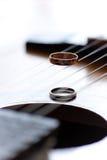 Zwei Hochzeitsringe sind auf Gitarrenstreifen Stockbilder