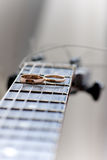 Zwei Hochzeitsringe sind auf Gitarrenstreifen Stockbild