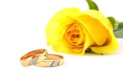 Zwei Hochzeitsringe und -GELB stiegen Stockbild