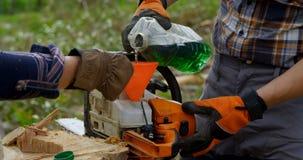 Zwei Holzfäller, die Motor wieder tanken, sahen im Wald 4k stock footage
