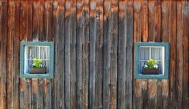 Zwei Holzkistefenster eines rustikalen Holzhauses stockfotografie