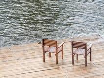 Zwei Holzstühle auf Bretterboden und Fluss Stockfotografie