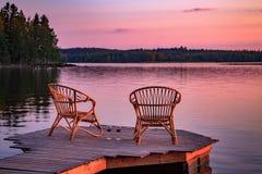 Zwei Holzstühle auf einem hölzernen Pier, der einen See bei Sonnenuntergang übersieht Stockfotos