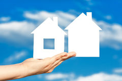 Zwei Häuser auf der Hand auf blauem Himmel Stockbild
