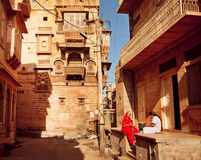 Zwei indische Frauen, die nahe dem Haus in der schmalen Straße sprechen Lizenzfreies Stockbild