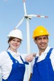 Zwei Ingenieure, die mit Windkraftanlage und Sonnenkollektoren aufwerfen stockfotos
