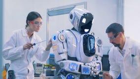 Zwei Ingenieure reparieren einen menschlich ähnlichen Roboter stock footage