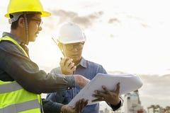 Zwei Ingenieure sind in der Steuerung unter Verwendung der Funkverbindungswerkzeuge und stockbild