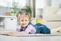 Zwei Jahre alte Baby liegt auf dem Boden Stockfotografie