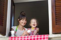 Zwei Jahre alte blonde Lachen mit ihrer Mutter, die auf Fensterbrett mit weißer Kaffeetasse und italienischem Metall-moka Topf si Lizenzfreie Stockbilder