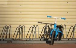 Zwei Jahre alte Junge, die sein blaues Fahrrad ohne Pedale in einem Fahrradpark parken lizenzfreies stockfoto