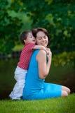 Zwei Jahre alte Junge umarmt seine junge Mamma im Park Lizenzfreie Stockfotos