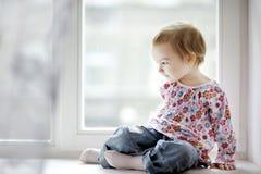 Zwei Jahre alte Mädchen, die durch das Fenster sitzen Lizenzfreie Stockfotos
