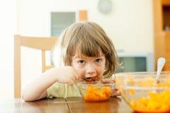 Zwei Jahre Kind isst Karottensalat Stockbild