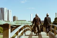 Zwei japanische Bauarbeiter, die eine Brücke in Hamarikyu-Gärten, Tokyo, Japan kreuzen Stockfotografie