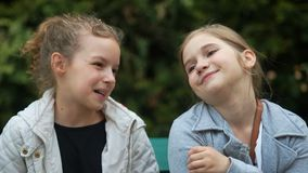 Zwei jugendlich Freundin-Lachen Zwei Jugendlichfreundinnen im Park Gl?ckliches junges M?dchen, das Taschen auf einem wei?en Hinte stock video