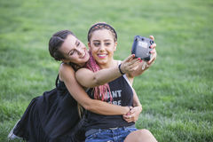 Zwei jugendlich Freundinnen, die ein Foto mit einer Kamera machen Lizenzfreie Stockfotografie