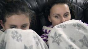 Zwei jugendlich Mädchen in den pijamas, die auf der Couch mit Decke sitzen Lizenzfreie Stockbilder
