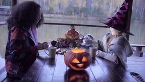 Zwei jugendlich Mädchen, die Süßes sonst gibt's Saures candys nach an Halloween teilen stock footage