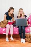Zwei jugendlich Mädchen, die zusammen Hausarbeit machen Stockbilder