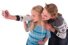 Zwei jugendlich Mädchen machen selfie auf einem weißen Hintergrund stockfotos