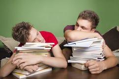 Zwei Jugendliche, die auf Büchern schlafen Stockfotografie